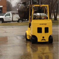 A forklift performing a drop test of materials.